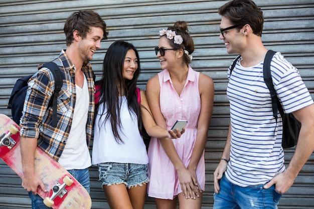 Hip przyjaciele patrząc na smartphone i opierając się toczenia drzwi Premium Zdjęcia