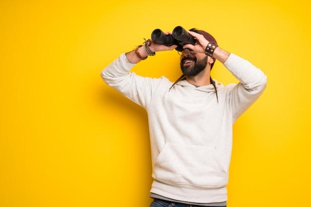 Hipis człowiek z dredami i patrząc w dal z lornetką Premium Zdjęcia
