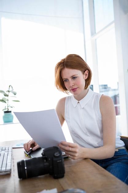 Hipster biznes kobieta siedzi przy biurku, czytanie plików Premium Zdjęcia