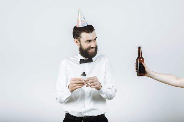 Hipster Szczęśliwy Brodaty Mężczyzna W Czapce Strony, Trzymając Ciasto Ze świecą I Ręką Wyciągając Piwo Premium Zdjęcia