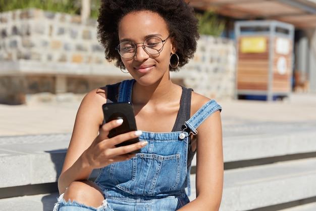 Hipster Z Ciemną Skórą, świeżymi Włosami, Odbiera Wiadomość Tekstową Na Telefon Komórkowy, Nosi Dżinsowe Ogrodniczki, Okulary Optyczne, Okrągłe Kolczyki, Ogląda Filmy W Internecie, Relaksuje Się Na świeżym Powietrzu, Robi Zakupy Online Darmowe Zdjęcia