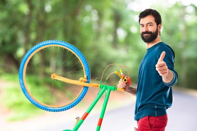 Hipster z kciuk trzyma rower Darmowe Zdjęcia