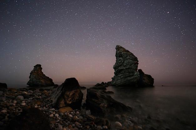 Hiszpania, malaga, nerja, molino de papel: gwiaździsta noc na plaży ze skałami Premium Zdjęcia