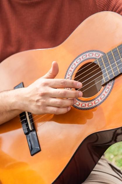 Hiszpanin Młody Człowiek Gra Na Gitarze, Siedząc W Parku Premium Zdjęcia