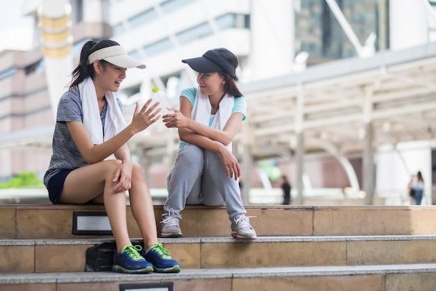 Hojna dziewczyna daje butelkę wody przyjacielowi przed godz Premium Zdjęcia