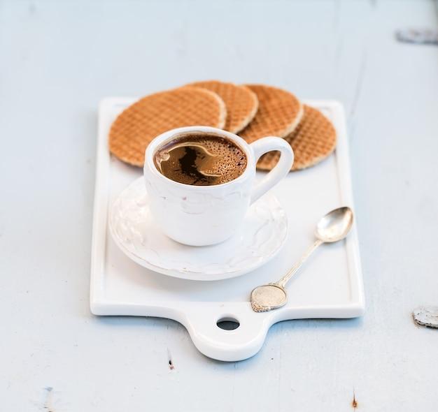 Holenderskie Stroopwafele Karmelowe I Filiżankę Czarnej Kawy Na Białej Ceramicznej Porcji Na Jasnoniebieskim Drewnianym Tle Premium Zdjęcia