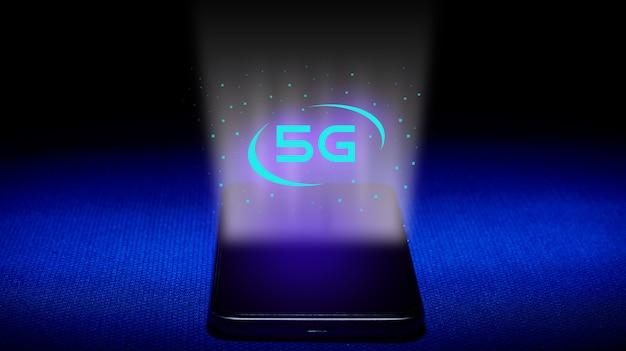 Hologram 5g. Smartfon I Obraz Hologramu 5g Na Niebieskim Tle. Koncepcja Technologii 5g To Nowa Generacja Sieci. - Wizerunek Premium Zdjęcia