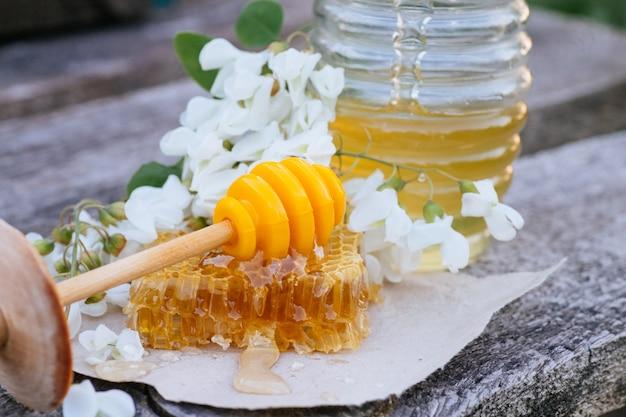 Honey Stick Leży Na Kawałku Odciętego świeżego Miodu W Plastrach Miodu. Premium Zdjęcia