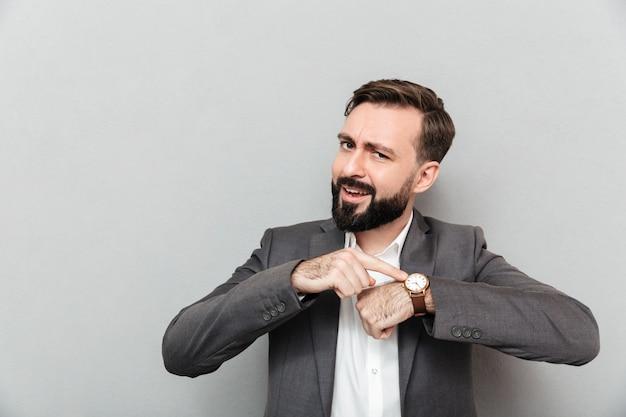Horyzontalny Brodaty Mężczyzna Wskazuje Przy Jego Wristwatch, Pozuje Odizolowywam Nad Popielatym Darmowe Zdjęcia