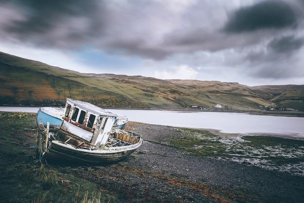 Horyzontalny Strzał Plaża Z Zaniechaną łodzią Blisko Wody Darmowe Zdjęcia