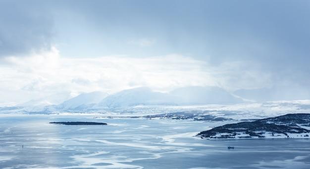 Horyzontalny Strzał Zbiornik Wodny Pokryty Lodem Otoczony Górami Pod Białymi Chmurami Darmowe Zdjęcia