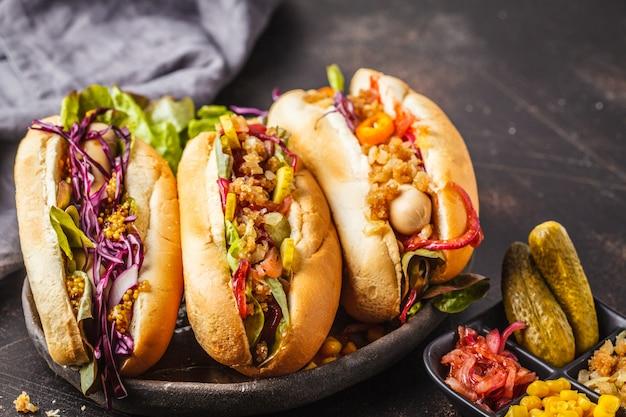 Hot dogi z asortowanymi polewami na ciemnym tle, odgórny widok. Premium Zdjęcia