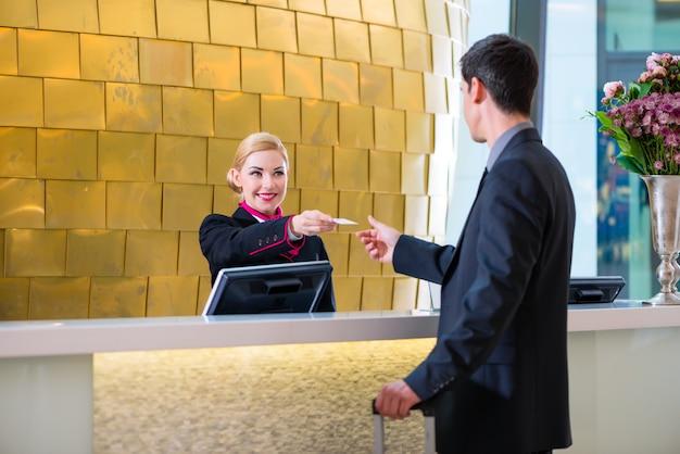 Hotelowy recepcjonista sprawdza w mężczyzna daje kluczowej karcie Premium Zdjęcia