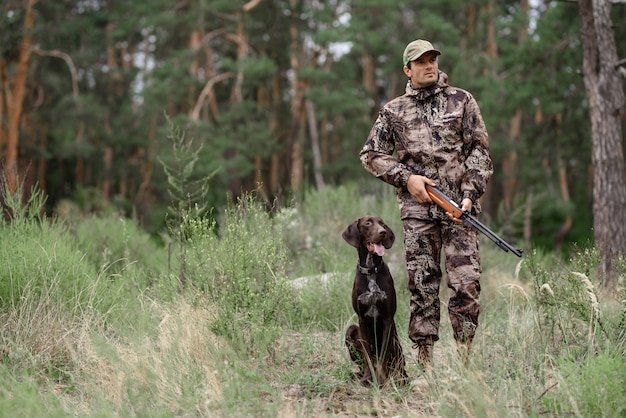Hunter with rifle walking przez forest pointer dog. Premium Zdjęcia