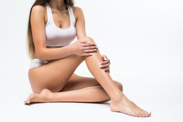 Idealne Ciało, Piękna Kobieta. Model Dziewczyna Z Pięknym Ciałem - Nogi, Ramiona, Ramiona, Siedząc Na Podłodze. Zdrowie I Uroda Kobieta W Białej Bieliźnie Dotykając Jej Skóry. Darmowe Zdjęcia
