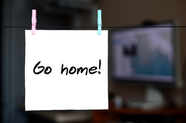 Idź Do Domu! Uwaga Jest Napisana Na Białej Naklejce, Która Wisi Na Sznurku Na Tle Wnętrza Biura Premium Zdjęcia