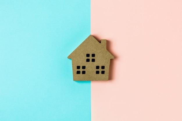 Ikona brązowy drewno do domu na niebieskim i różowym tle Premium Zdjęcia