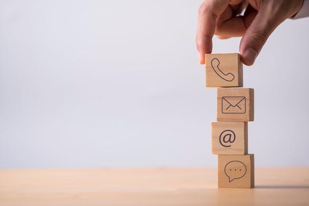 Ikona Ręcznego Wprowadzania Kontaktu Biznesowego Zawiera Adres E-mail Numeru Telefonu I Wiadomości, Które Drukują Ekran Na Drewnianej Kostce. Premium Zdjęcia