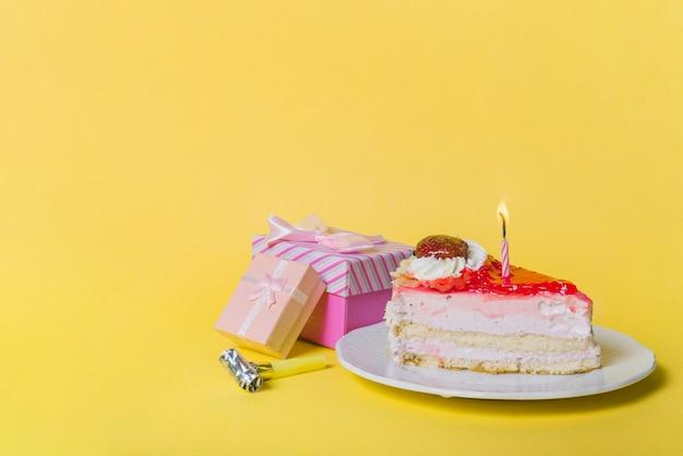 Iluminująca świeczka Na Plasterka Torcie Z Dwa Prezentów Pudełkami I Partyjnej Dmuchawą Przeciw żółtemu Tłu Darmowe Zdjęcia