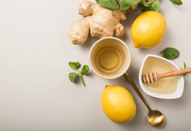 Imbirowa Herbata Cytrynowa Z Miodem. Rozgrzewająca Herbata Wzmacniająca Odporność Z Cytrusami I Imbirem. Puchar, Miód, Korzeń Imbiru Na Szarym Pastelowym Tle Premium Zdjęcia