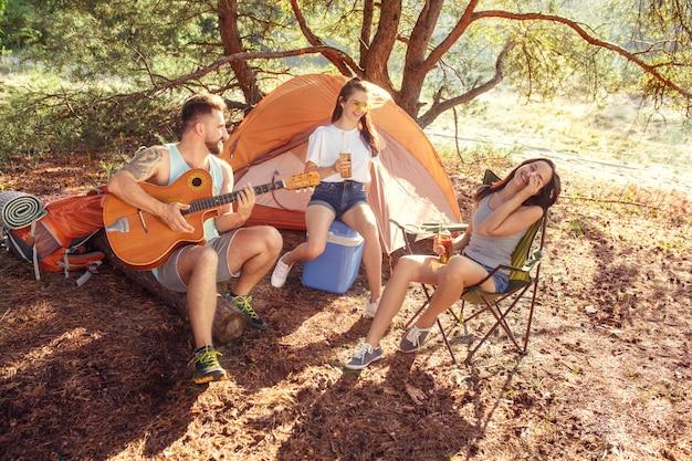 Impreza, Camping Grupy Kobiet I Mężczyzn W Lesie. Relaksują Się, śpiewając Piosenkę Darmowe Zdjęcia