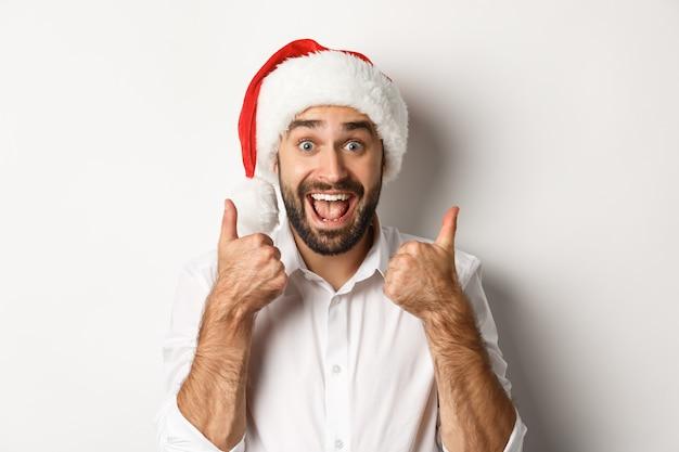 Impreza, Ferie Zimowe I Koncepcja Uroczystości. Mężczyzna Korzystających Ze świąt Bożego Narodzenia, Ubrany W Santa Hat I Pokazujący Kciuk Z Podekscytowaną Twarzą Darmowe Zdjęcia