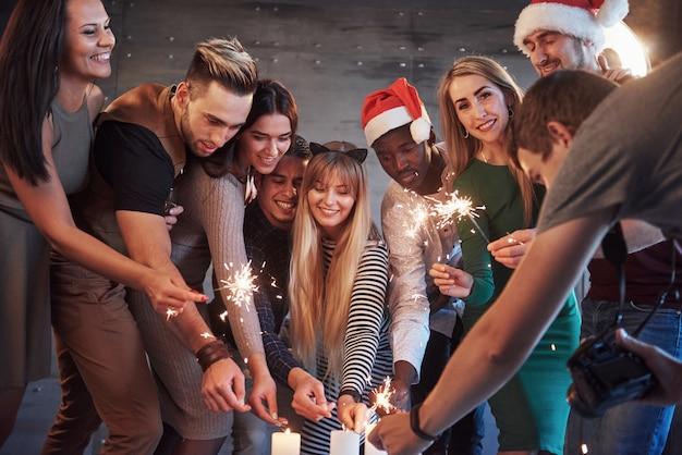 Imprezuj z przyjaciółmi. grupa wesoły młodych ludzi niosących ognie i szampana Premium Zdjęcia