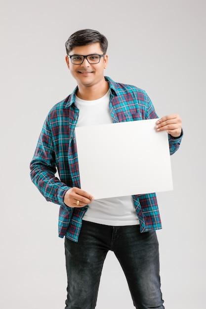 Indian, azjatycki młody człowiek pokazujący puste szyld Premium Zdjęcia
