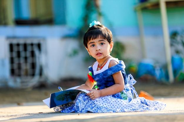 Indianka little girl dziecko pisze na notatce książki, studiuje Premium Zdjęcia