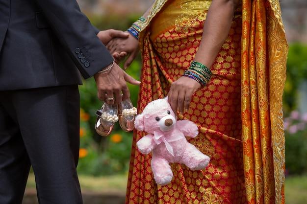 Indianka W Ciąży I Jej Mąż, Trzymając Zabawki Dla Niemowląt Premium Zdjęcia