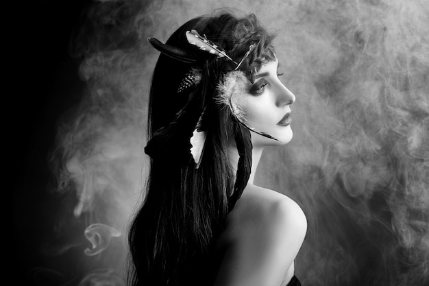 Indianka Z Piórami We Włosach, Portret Kobiety Indian Amerykańskich Piękna W Dymie. Piękna Twarz Z Czystą Skórą, Kontrastowy Makijaż Premium Zdjęcia