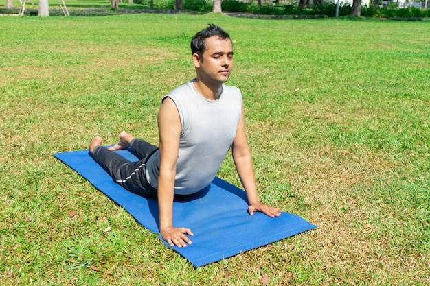 Indiański mężczyzna robi oddolnej obszycie psa pozie outdoors na zielonym gazonie. outdoor jogi koncepcji Darmowe Zdjęcia