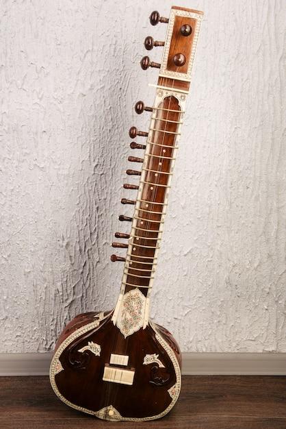 Indyjski Instrument Muzyczny Sitar Stojący Obok Szarej ściany Premium Zdjęcia