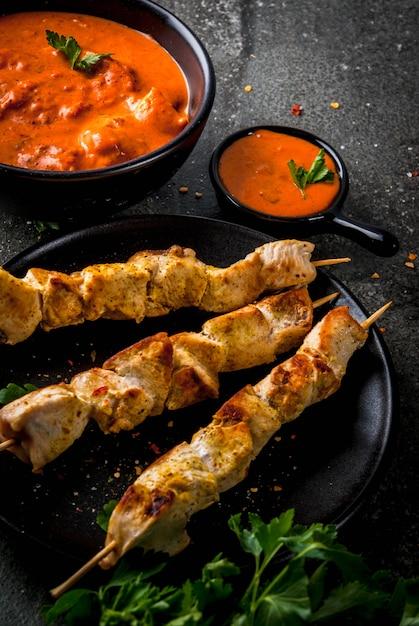 Indyjskie Jedzenie. Tradycyjne Danie Pikantne Tikka Masala Z Kurczaka, Curry Z Masła, Z Indyjskim Chlebem Maślanym, Przyprawami, Ziołami Premium Zdjęcia