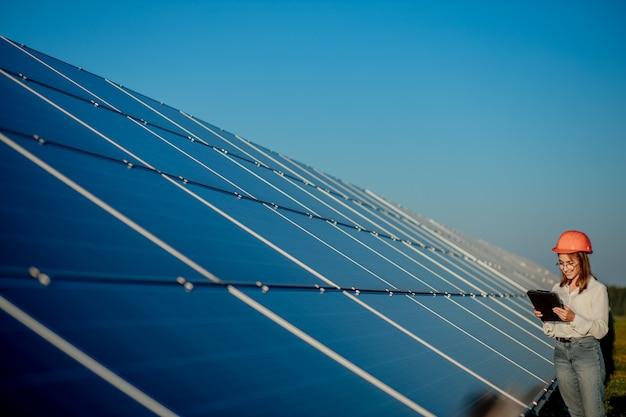 Inspektor Inżynier Kobieta Trzymając Cyfrowy Tablet Pracujący W Farmie Paneli Słonecznych, Park Ogniw Fotowoltaicznych, Koncepcja Zielonej Energii. Premium Zdjęcia