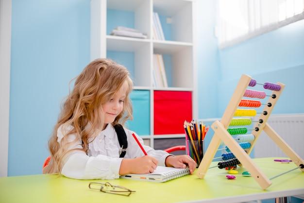 Inspirowana mała dziewczynka przy stole z kredkami. biurko szkolne z przyborami szkolnymi, ołówkami, torbami, zeszytem i liczydłem. mała blond dziewczyna jest ubranym szkła z powrotem szkoły pojęcie. Premium Zdjęcia
