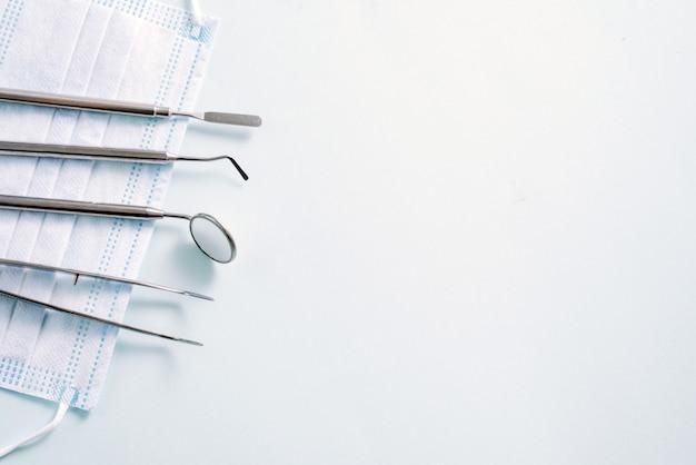 Instrumenty Dentystyczne: Lustro I Sonda Dentystyczna Leżące W Lewo Na Masce Medycznej Na Jasnoniebieskim Tle. Wzór Na Reklamę Premium Zdjęcia