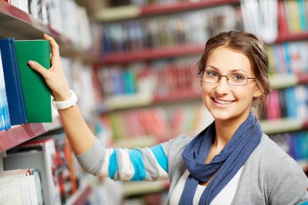 Inteligentna Dziewczyna Biorąc Książkę Z Półki Darmowe Zdjęcia