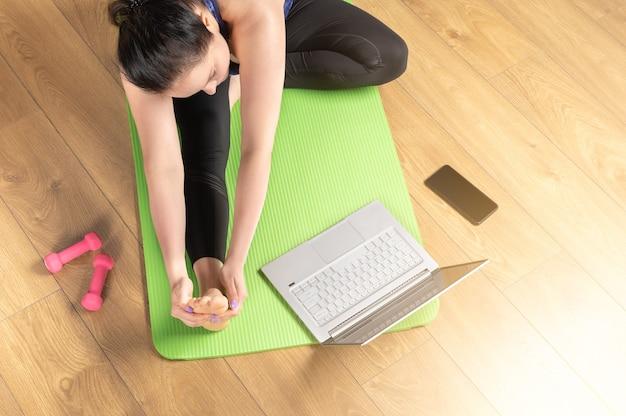 Internetowy Laptop Yoga Home. Widok Z Góry Kobiety Praktykujących Jogę Na Macie Do Jogi Z Laptopem. Kobieta W średnim Wieku Medytuje I Relaksuje Się Podczas Treningu Wideo W Domu. Premium Zdjęcia