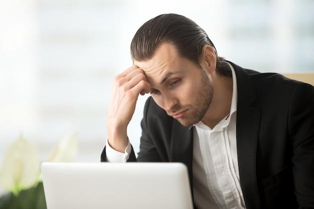 Intrygujący młody biznesmen patrzeje laptopu ekran Darmowe Zdjęcia