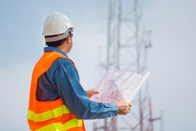 Inżynier Lub Technik Przygotuj Plan I Spójrz Na Podstawę Wieży Telekomunikacyjnej Premium Zdjęcia