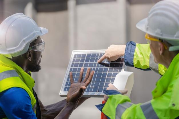 Inżynier, Pracownik Fabryki, Pokazuje I Sprawdza Panel Ogniw Słonecznych Pod Kątem Zrównoważonej Technologii, Kombinezon Roboczy I Hełm. Premium Zdjęcia