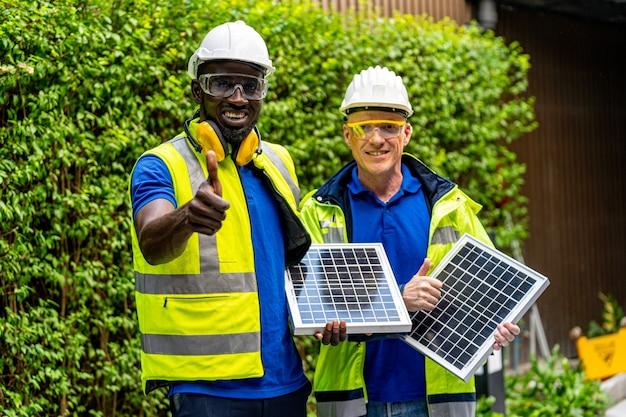 Inżynier, Pracownik Fabryki, Pokazuje I Sprawdza Panel Ogniw Słonecznych Pod Kątem Zrównoważonej Technologii Z Zielonym Zestawem Roboczym Premium Zdjęcia