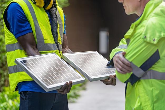 Inżynier, Pracownik Fabryki, Pokazuje I Sprawdza Panel Ogniw Słonecznych Pod Kątem Zrównoważonej Technologii. Premium Zdjęcia
