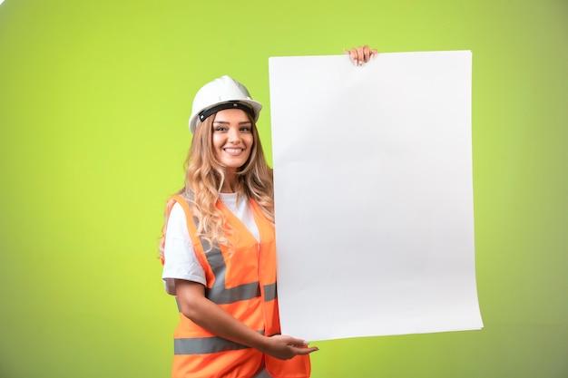 Inżynier W Białym Hełmie I Stroju Przedstawiającym Plan Budowy I Normy. Darmowe Zdjęcia
