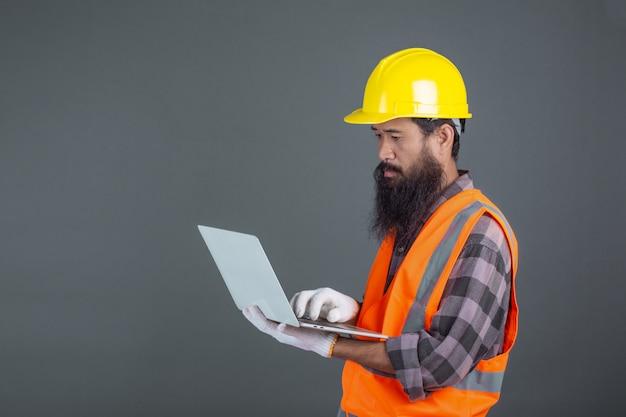 Inżynier w żółtym hełmie z notatnikiem na szaro. Darmowe Zdjęcia
