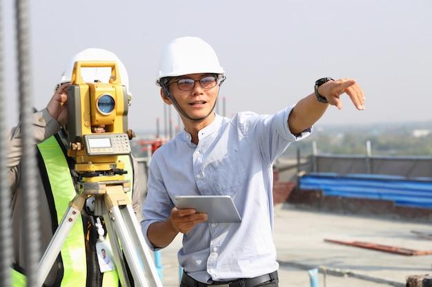 Inżynierowie I Personel Kontrolują Budynki Za Pomocą Teodolitu. Premium Zdjęcia