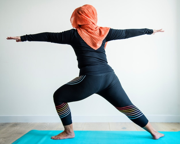 Islamska kobieta robi joga w pokoju Premium Zdjęcia