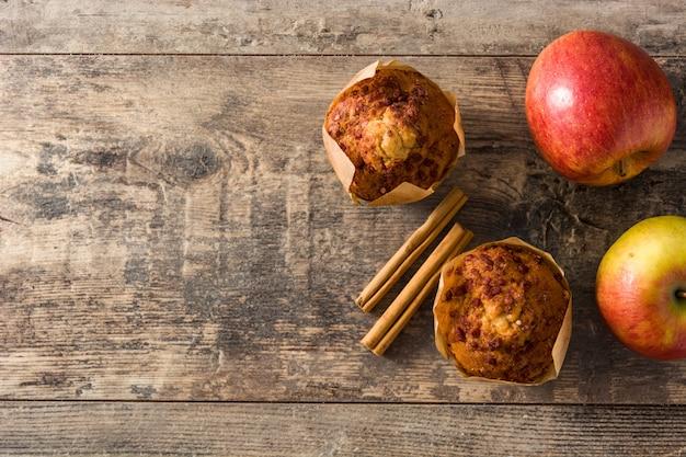 Jabłka i cynamonowi muffins na drewnianym stole. widok z góry. skopiuj miejsce Premium Zdjęcia