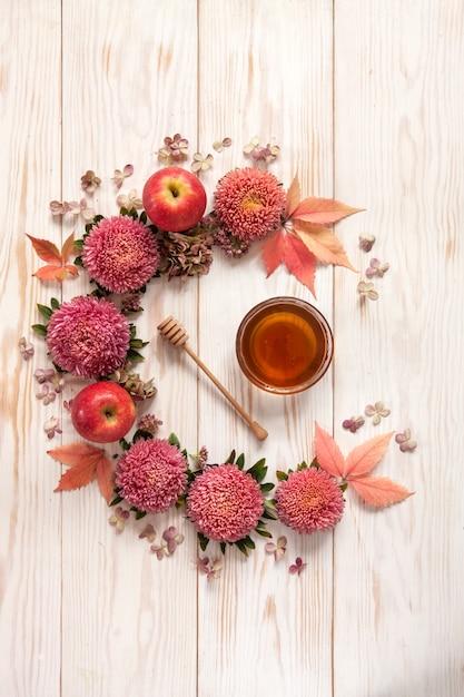 Jabłka, różowe kwiaty i miód z przestrzenią kopii tworzą kwiatową dekorację. Premium Zdjęcia